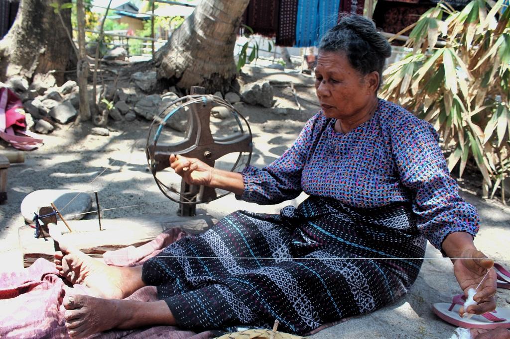 Seorang perajin tenun dari Sikka, Maumere, sedang memintal benang