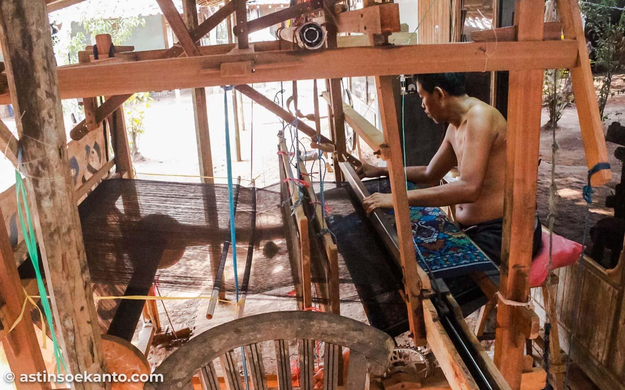 Perajin tenun pria sedang tekun bekerja
